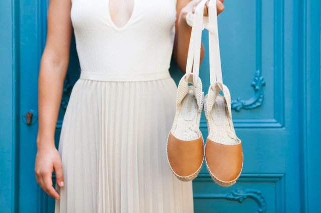 woman holding pair of espadrille shoes