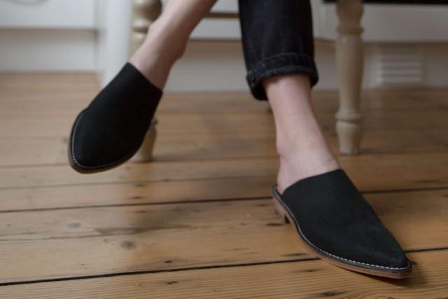 woman wearing black slip on shoes