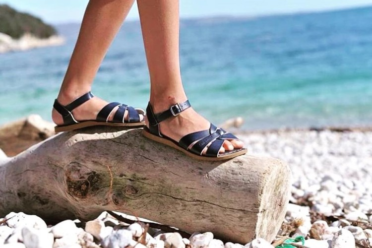 woman on beach in black sandals