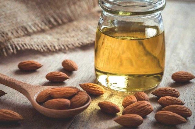jar of almond oil, almond nuts and a spoon