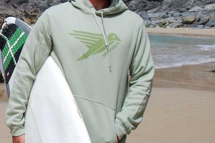 Man in pale green hoodie with surf board