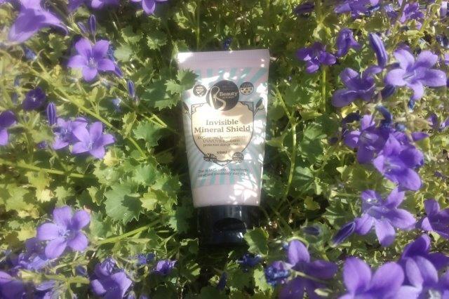 tube of sunscreen sitting amongst in purple flowers