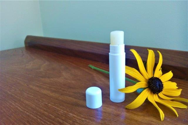 tube of lipbalm and flower on wooden table