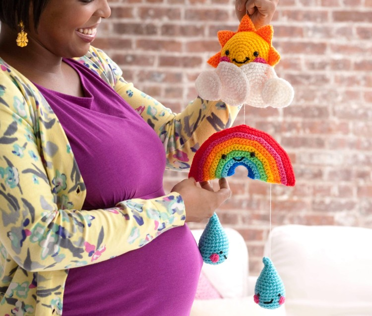 pregnant woman holding crocheted mobile