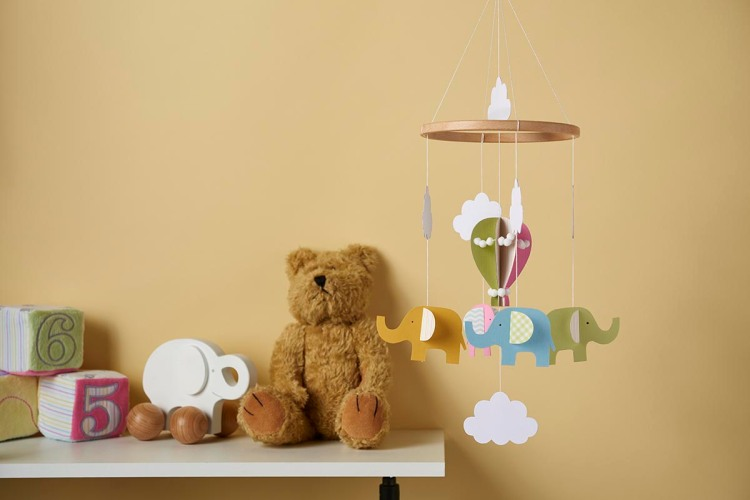 baby mobile beside teddy